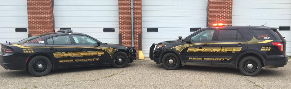 Two police vehicles parked in front of garage