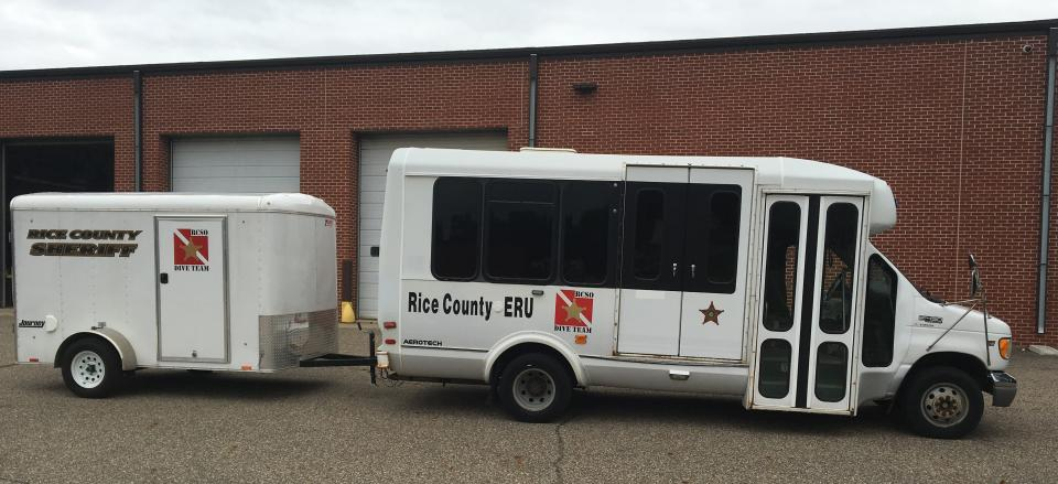 Rice County ERU van and trailer parked in front of garage