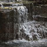 Image of water rushing through rocky waterfall into pond below