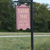 Image of the reddish brown Caron Park sign with yellow lettering