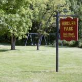 Image of the reddish brown Hirdler Park sign with yellow lettering