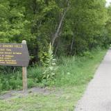 Image of a paved walking trail with sign on right side