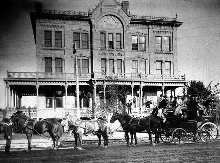 Black and white image of a six-horse buggy with passengers in front of the three story Brunswick Hotel in 1885