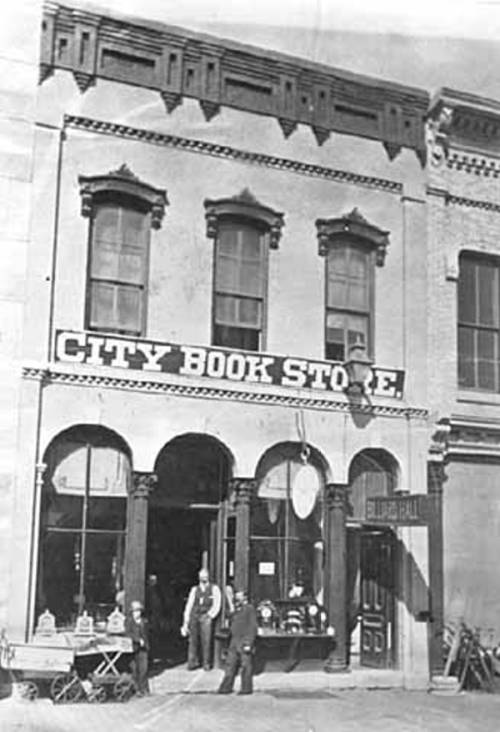 Black and white image of a city two story building, two men stand out front of a doorway with a sign above the door saying City Book Store