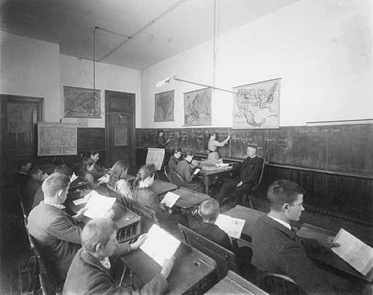 Black and white image of students in a classroom with a teacher at the blackboard from the Deaf School Classroom (1892)