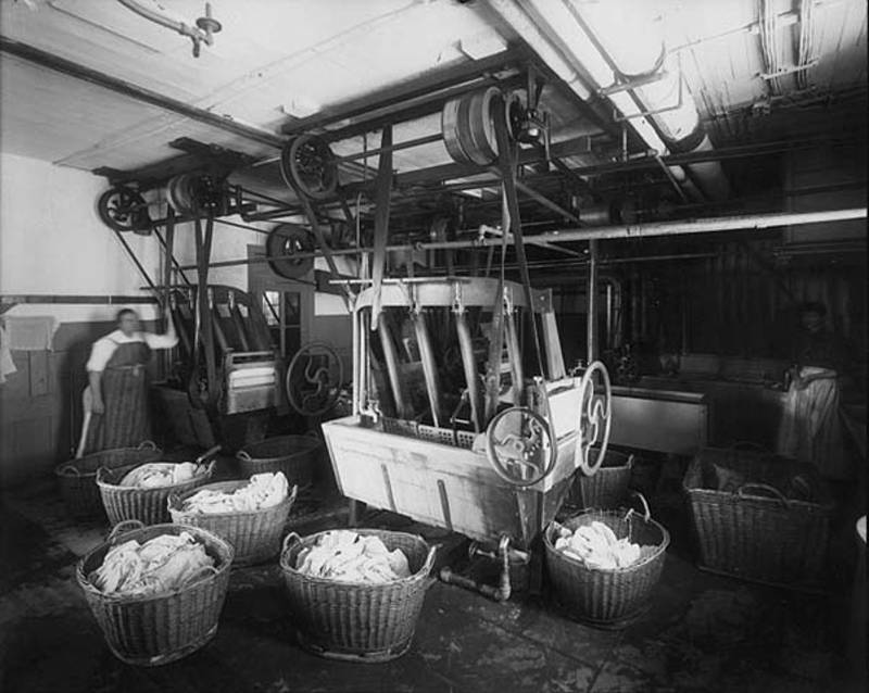 Black and white image of the laundry room with a worker and baskets of laundry at the Deaf School Laundry (1899)