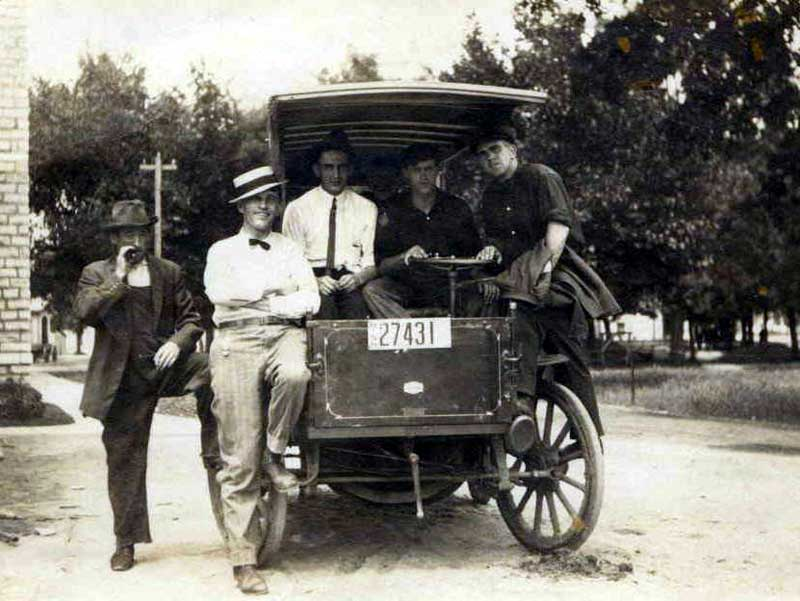 Black and white image of five young ment standing on and around an Early Automobile