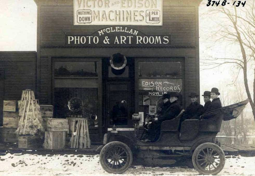 Black and white image of five people in an early car in front of the Edison Record Store