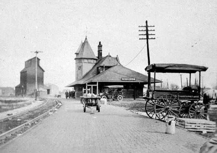 Black and white image of a sidewalk leading to the Faribault Depot (1912) with wagons