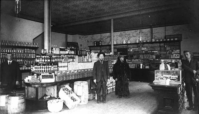 Black and white image of two men standing inside the Haskell Store (1900)