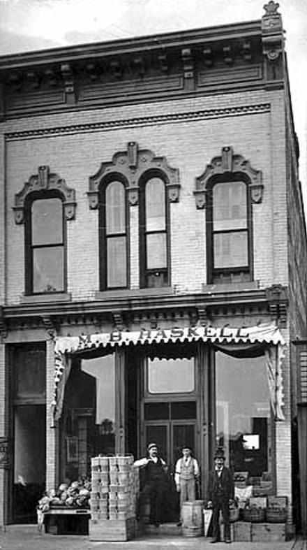 Black and white image of the facade of the Haskell Store (1910) with three men stading out front