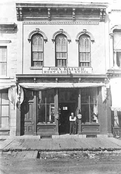 Black and white image of a man standing in a building's doorway, with a sign above the door saying John Kaiser Boot & shoe store