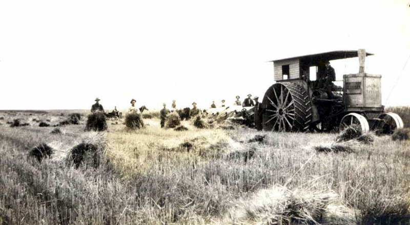 Black and white with sepia tone image of men bailing hay in the fields with a tractor in front