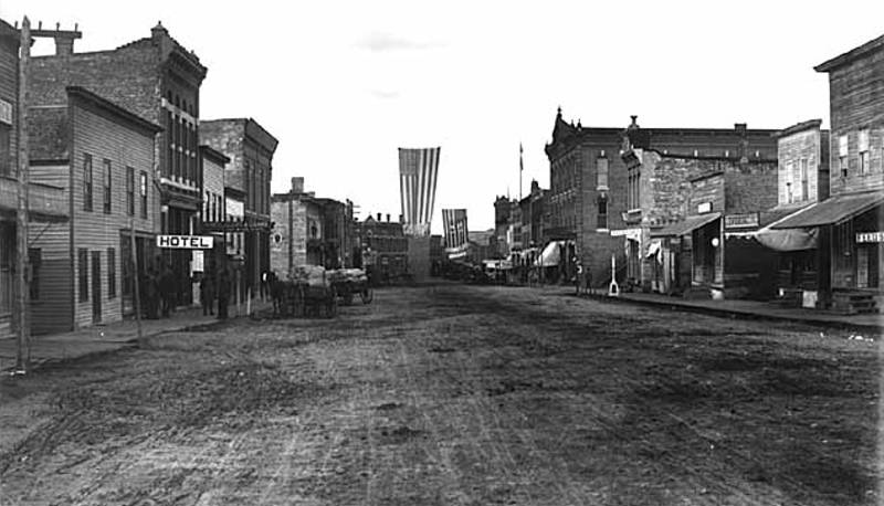 Black and white image of Northfield Street with building on either side and and American flag (1900)