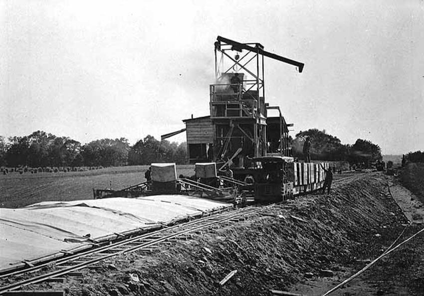 Black and white image of a machine paving a road, with small working railroad alongside