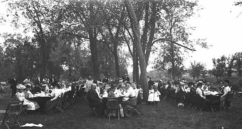 Black and whiet image of many people seated at long tables under trees titled Picnic Gathering (1908)