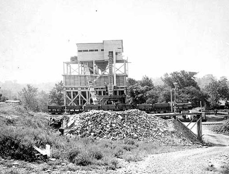 Black and white image of the building at the quarry with rocks from 1920
