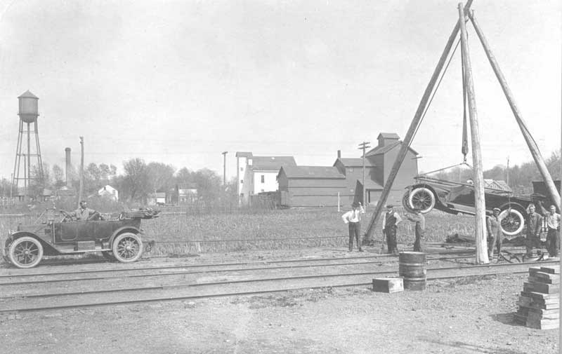 Black and white image of a tripod type crane removing auto from Railroad