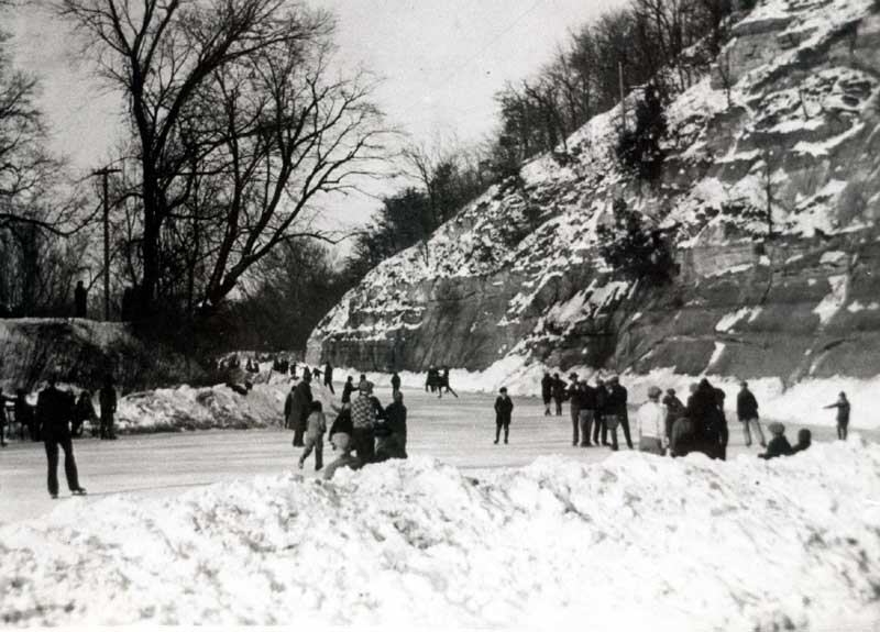 Black and white photo of people ice skating on a frozen pond with a rock face to the right