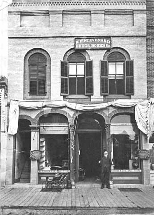 Black and white image of a man standing in the doorway of a two story building with a sign saying Stevens Drug Store (1881)