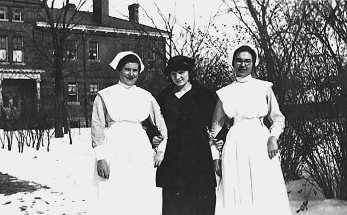 Black and white image of three Student Nurses in the snow in front of a building (1915)