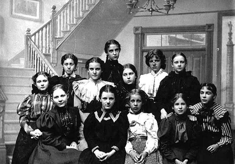 Black and white image of twelve girls standing and sitting in front of a stairway, titled Sunday School Class Emma Lincoln (1898)