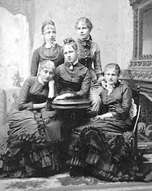 Black and white photo of five women standing and sitting around a table in formal dress in 1879