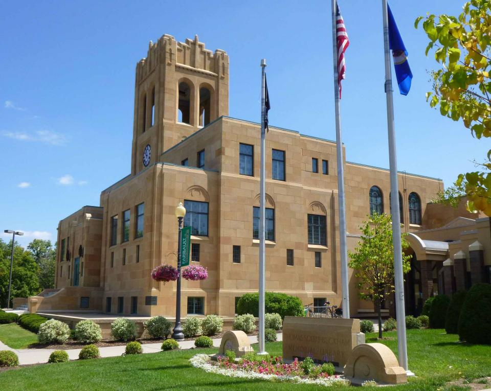 Modern image of the stone Buckham Memorial Library with flags out front and bell tower