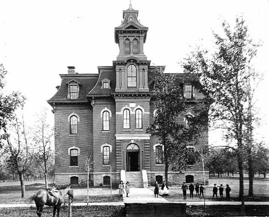 Black and white image of students walking around the four story stone Central School at Northfeild in 1880