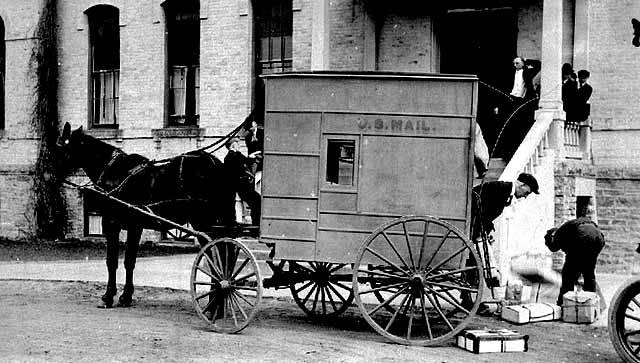 Black and white image of a horse drawn US Mail wagon making a delivery in 1916