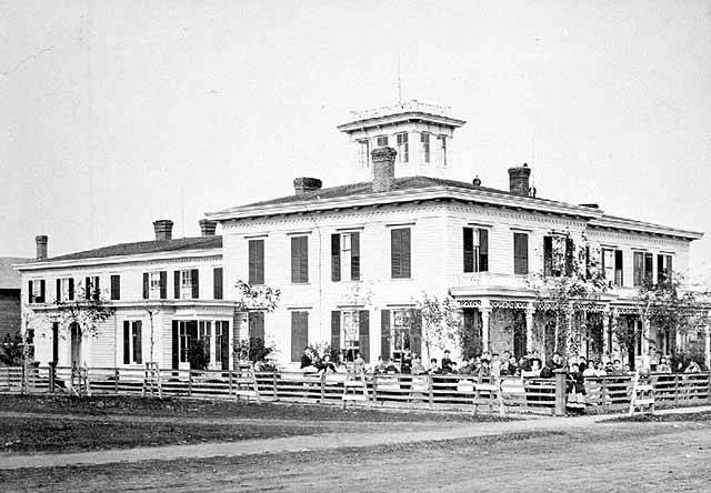 Black and white image of the two story white St. Mary's School building with people sitting at tables in the lawn