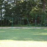 Image of a metal swingset in a meadow